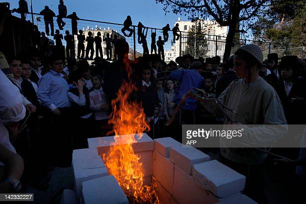 Ultra orthodox Jewish children gather around a burning mock Temple altar lit for a ritual slaughter in preparation for the renewal of the Passover...