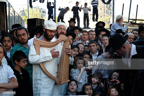 Ultra orthodox Jewish children gather around as members of the Temple Institute dressed in biblical priestly garments sing and play at the start of a...