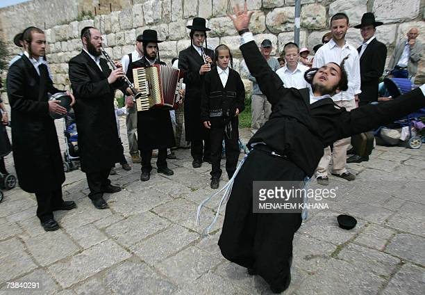 Ultra Orthodox Jewish Klezemer band members play music and dance as they march next to the walls of Jerusalem old city during the Jewish Passover...