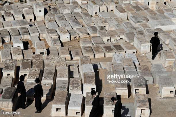 Ultra Orthodox Jewish men walk between tombs at the Mount of Olives Jewish cemetary, in front of Jerusalem's Old City on February 12, 2019.