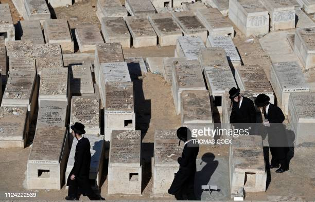 TOPSHOT Ultra Orthodox Jewish men walk between tombs at the Mount of Olives Jewish cemetary in front of Jerusalem's Old City on February 12 2019