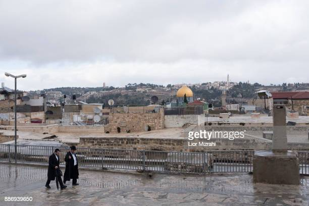 Ultra Orthodox Jewish men walk on a roof at the Old City with a view of the golden Dome of the Rock Islamic shrine on the back on December 6, 2017 in...