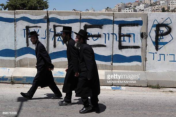 Ultra Orthodox Jewish men walk past settlers and anti settler�s graffiti during their pilgrimage to the Tomb of the Patriarchs holy to both Jews and...