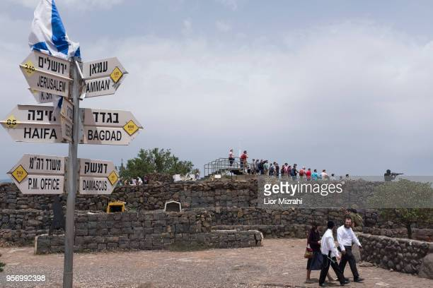 Ultra Orthodox jews and tourists gather next to signs pointing out distances to different cities on Mount Bental next to the Syrian border on May 10...