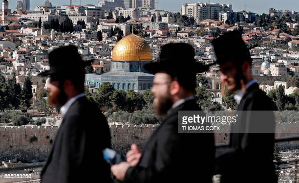 TOPSHOT Ultra Orthodox Jews are seen walking in the city of Jerusalem in the Mount of Olives area with the Dome of the Rock mosque in the background...