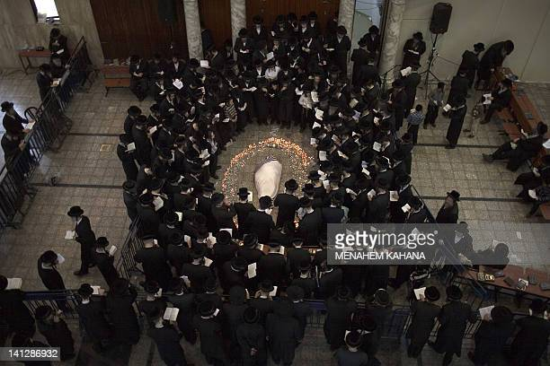 Ultra Orthodox Jews from the Vizhnitz Hasidic dynasty pray and light candles around their rabbi Moshe Yhoshua Hager's body wrapped in a prayer Shawl...