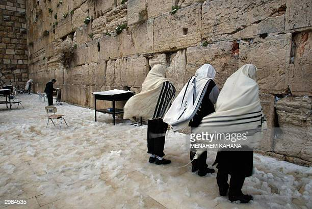Ultra orthodox Jews hold the morning prayer at the snowed Western Wall in the old city of Jerusalem 15 February 2004 Around nine centimeters of snow...