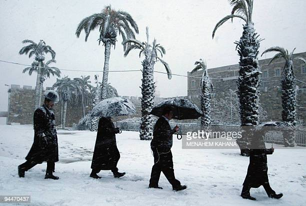 Ultra Orthodox Jews walk during a snow storm outside the walls of Jerusalem's Old City 25 February 2003 Heavy snowfall hit Jerusalem Amman and the...