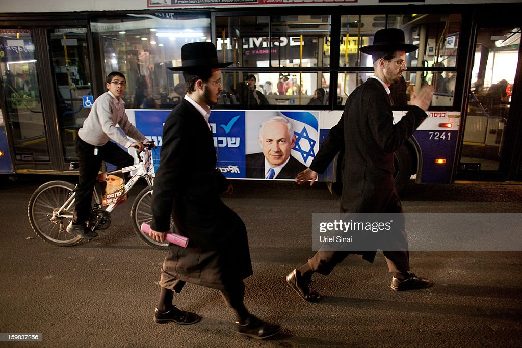 Ultra Orthodox Jews walk past a bus as an election poster of Israeli Prime Minister Benjamin Netanyahu hang on it, ahead of the upcoming Israeli elections on January 21, 2013 in Bnei Brak, Israel. Israeli elections are scheduled for January 22 and so far showing a majority for the Israeli right.