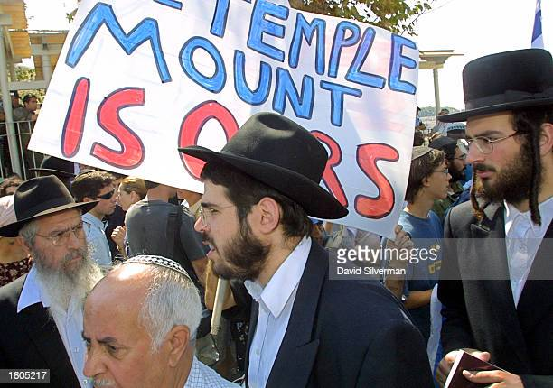 Ultra Orthodox Jews walk past a demonstration held by a Jewish group known as the Temple Mount Faithful July 29 2001 in Jerusalem