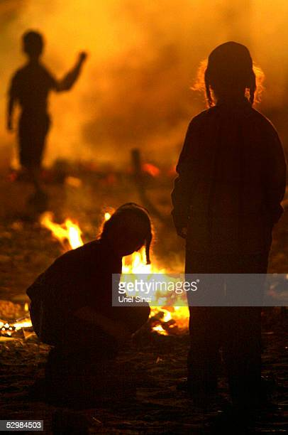 Ultra Ortodox Israelis are silhouetted by a bonfire during Lag BaOmer festivities May 26 2005 in Bnei Brak Israel Israelis celebrate the Jewish...