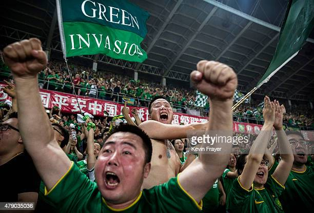 Ultra supporters and fans of the Beijing Guoan FC celebrate together after a goal against Chongcing Lifan FC during their Chinese Super League match...