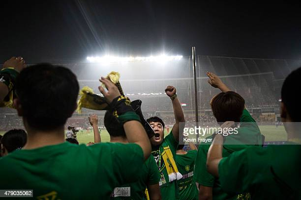 Ultra supporters and fans of the Beijing Guoan FC chant slogans during a match against Chongcing Lifan FC in Chinese Super League play on June 28...