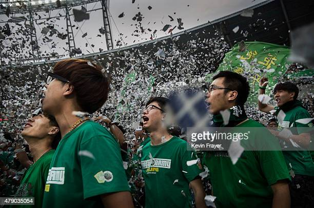 Ultra supporters of the Beijing Guoan FC cheer during a match against Chongcing Lifan FC in Chinese Super League play on June 28 2015 in Beijing...