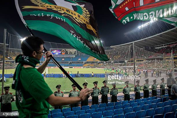 Ultra supporters of the Beijing Guoan FC wave flags as police stand guard during their Chinese Super League match against Tianjin FC on June 20 2015...
