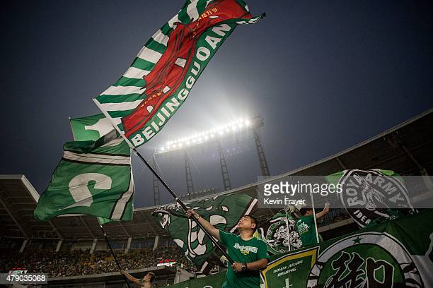 Ultra supporters of the Beijing Guoan FC wave flags during their match against Chongcing Lifan FC in Chinese Super League play on June 28 2015 in...