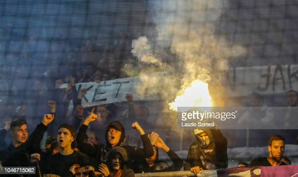 Ultra supporters of Ujpest FC lift up flaming torches during the Hungarian OTP Bank Liga match between Ferencvarosi TC and Ujpest FC at Groupama...