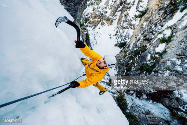 ultra wide angle shot of ice climber hanging from side of a 100 meter tall frozen waterfall with ice axes - danger stock pictures, royalty-free photos & images