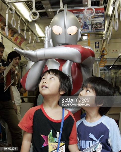 Ultraman Jack poses with young fans during a press preview inside a train in Tokyo, 17 July 2006. The event was held to commemorate the 40th...