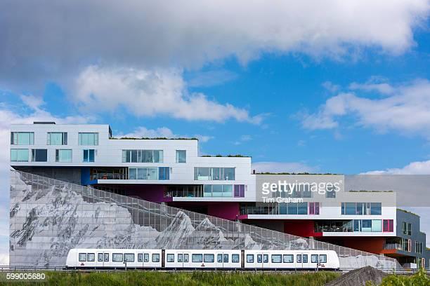 Ultramodern new apartments with mountain range below and train on Orestads Boulevard on June 22 2015 in Copenhagen Denmark