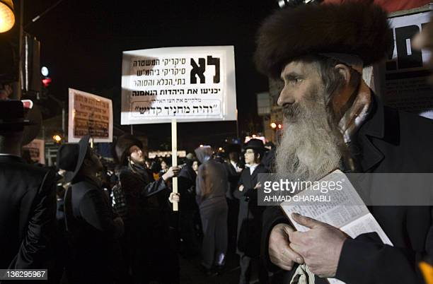 UltraOrthodox Jew hold banners as they gather during a protest in Jerusalem's Mea Shearim neighborhood on December 31 denouncing what they call the...