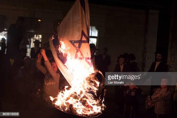 UltraOrthodox Jewish children burn an Israeli flag at Lag BaOmer celebration on May 2 2018 in Jerusalem Israel The Lag BaOmer bonfire is lit to...