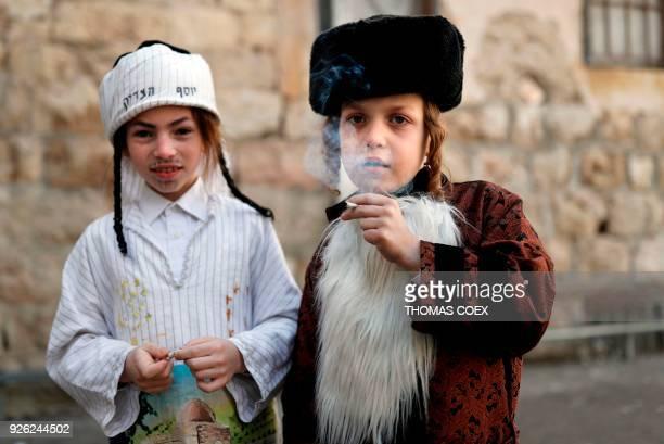 TOPSHOT UltraOrthodox Jewish children smoke a cigarette in Jerusalem's ultraorthodox neighbourhood of Mea Sharim on March 2 2018 during the holiday...