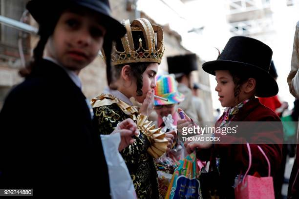 UltraOrthodox Jewish children smoke a cigarette in Jerusalem's ultraorthodox neighbourhood of Mea Sharim on March 2 2018 during the holiday of Purim...