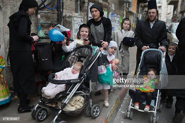 UltraOrthodox Jewish families dressed in costumes celebrate the Purim holiday in the ultraorthodox Mea Shearim neighborhood in Jerusalem on March 17...