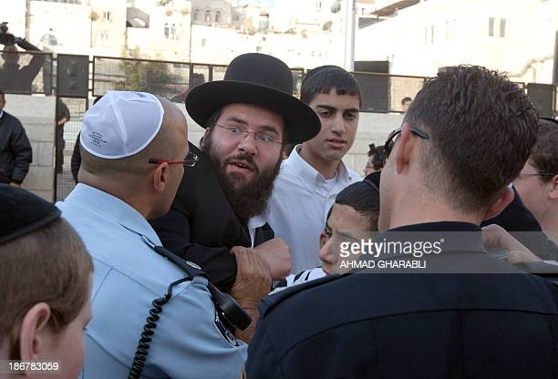 A UltraOrthodox Jewish man is moved away during a protest against members of the liberal Jewish religious group Women of the Wall who are wearing...