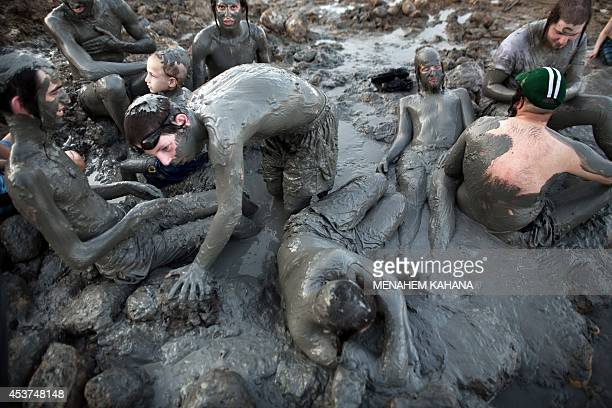 UltraOrthodox Jewish men and boys cover their bodies with mineralrich mud during their vacation at a Men's only beach on the shores of the northern...