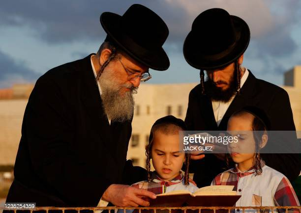 """Ultra-Orthodox Jewish men and children perform the """"Tashlich"""" ritual in the coastal city of Netanya on September 14, 2021 during which """"sins are cast..."""