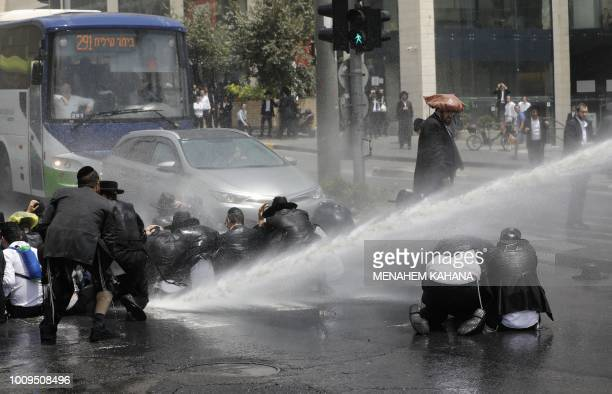 UltraOrthodox Jewish men are sprayed with water cannons by Israeli security forces during a protest in Jerusalem on August 2 2018 According to police...