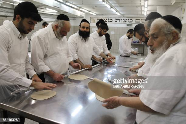 UltraOrthodox Jewish men knead the dough before baking Matzoth on April 4 2017 at a bakery in Jerusalem Religious Jews throughout the world eat...