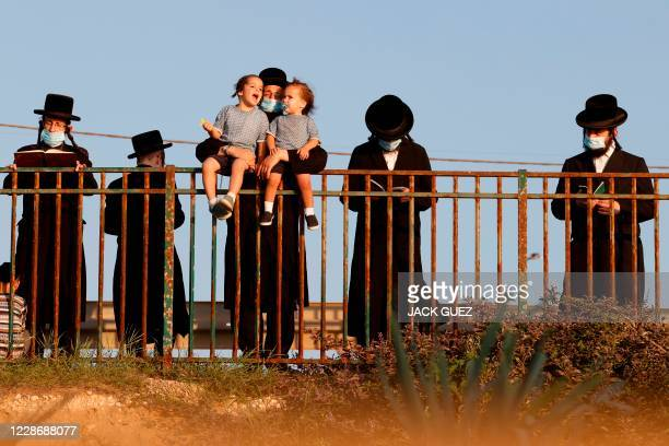 UltraOrthodox Jewish men perform the Tashlich ritual in the coastal city of Netanya on September 24 2020 during which sins are cast into the water to...