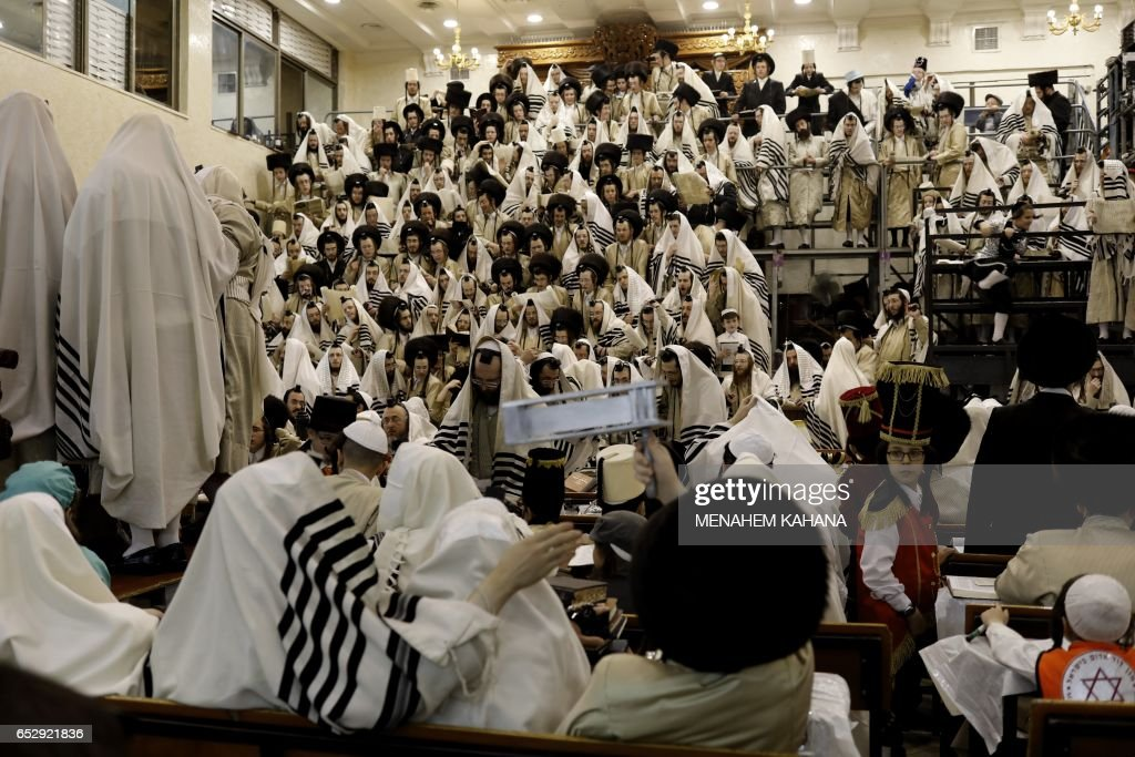 Ultra-Orthodox Jewish men read the book of Esther in their synagogue in Jerusalem's Mea Shearim ultra-Orthodox neighbourhood on March 13, 2017 during the religious holiday of Purim. The carnival-like Purim holiday is celebrated with parades and costume parties to commemorate the deliverance of the Jewish people from a plot to exterminate them in the ancient Persian Empire 2,500 years ago, as recorded in the Biblical Book of Esther. /