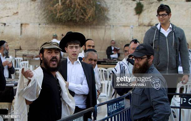 UltraOrthodox Jewish men shout during a protest against members of the liberal Jewish religious group Women of the Wall who are wearing phylacteries...