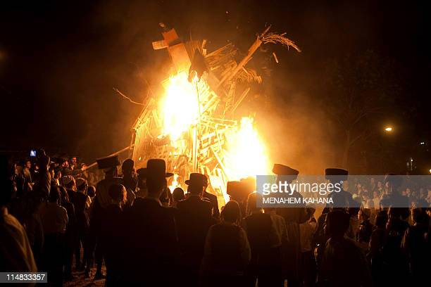 UltraOrthodox Jewish men stand beside a giant bonfire in the Mea Shearim neighborhood of Jerusalem on May 21 2011 during the celebration of Lag...