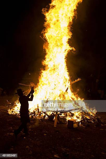 UltraOrthodox Jewish men stand beside a giant bonfire in the Mea Shearim neighborhood of Jerusalem on May 17 2014 during the celebration of Lag...
