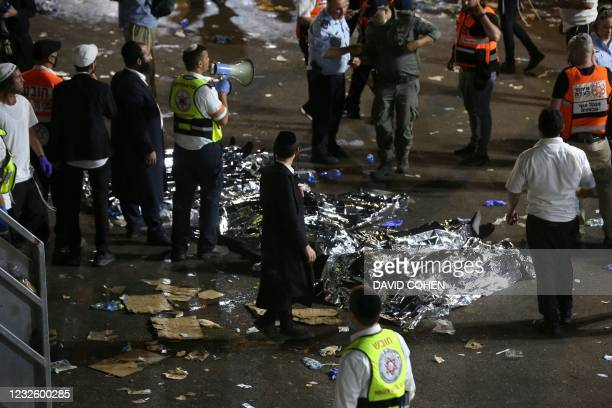 Ultra-Orthodox Jewish men stand next to covered bodies after dozens of people were killed and others injured after a grandstand collapsed in Meron,...