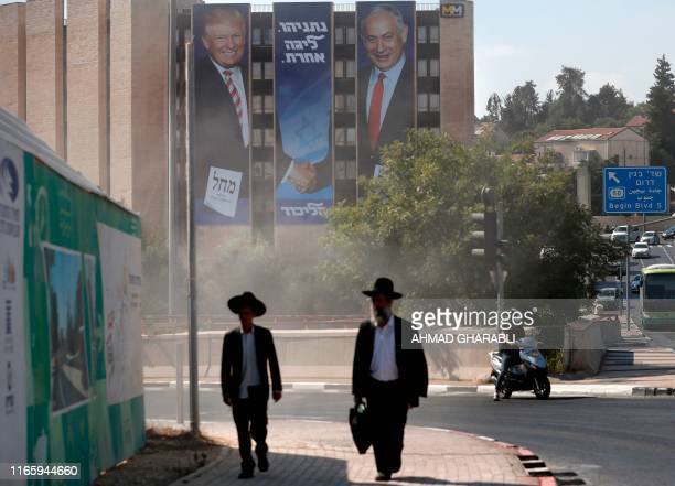 UltraOrthodox Jewish men walk along a street in Jerusalem on September 4 past an Israeli election banner for the Likud party showing US President...