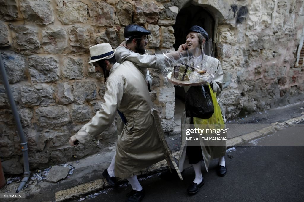 TOPSHOT - Ultra-Orthodox Jewish men walk in the street after getting drunk in Jerusalem's Mea Shearim ultra-Orthodox neighbourhood on March 13, 2017 during the religious holiday of Purim. The carnival-like Purim holiday is celebrated with parades and costume parties to commemorate the deliverance of the Jewish people from a plot to exterminate them in the ancient Persian Empire 2,500 years ago, as recorded in the Biblical Book of Esther. /
