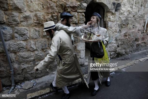 TOPSHOT UltraOrthodox Jewish men walk in the street after getting drunk in Jerusalem's Mea Shearim ultraOrthodox neighbourhood on March 13 2017...