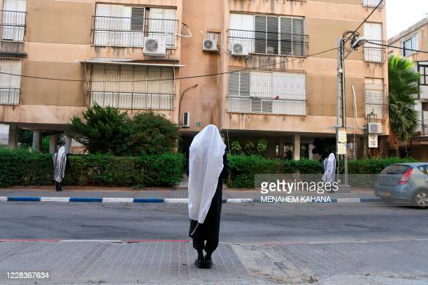 UltraOrthodox Jewish men wearing a protective face masks due to the COVID19 coronavirus pandemic and Talit prayer shawl keep a twometre distance as...