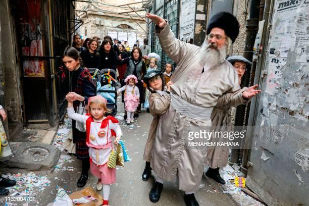 UltraOrthodox Jewish men wearing Purim costumes dance in the Jerusalem Mea Shaarim neighbourhood on March 22 2019 during the feast of Purim The...