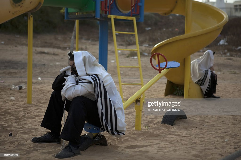 Ultra-Orthodox Jewish protesters, wrapped in prayer shawls, sit in a children's park following a protest against the removal of ancient tombs in the southern Israeli city of Ashkelon on May 16, 2010. Hundreds of ultra-Orthodox Jews also protested in Jerusalem and other religious neighborhoods in the country against the Israeli government's decision to relocate the tombs in order to erect on the site a new emergency ward for Ashkelon's Barzilai hospital. Under pressure from the religious Jews, who say the work would desecrate ancient tombs belonging to their ancestors, the government had frozen its plans before finally deciding to go ahead with the project.