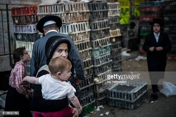 UltraOrthodox Jewish woman passes chickens being sold for the Kaparot ceremony on October 10 2016 in Jerusalem Israel It is believed that the Jewish...