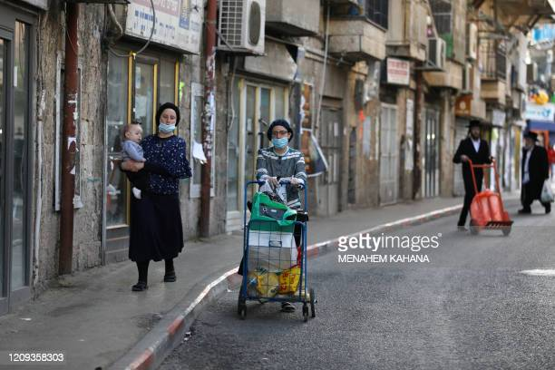 UltraOrthodox Jewish women wearing protective face masks walk down a street in Jerusalem's Mea Shearim neighbourhood on April 7 on the eve of the...