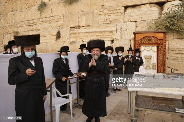 UltraOrthodox Jewish worshippers wearing protective face masks pray during the Sukkot holiday or the feast of the Tabernacles at the Western Wall in...