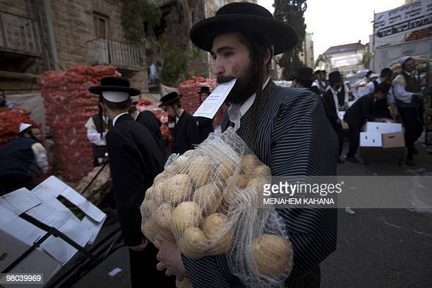 Ultra-Orthodox Jews carry donated food for poor families at a distribution center before Pesach holiday at a conservative Jerusalem neighbourhood on...